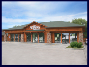 This beautiful ceder sided AuBurn Pharmacy has rock pillars and a green metal roof. The front has the white AuBurn Pharmacy logo.