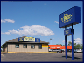 The tan Auburn Pharmacy in Abilene, Kansas, sits in front of Country Mart. There is a tall blue AuBurn Pharmacy sign in front of the pharmacy and a yellow AuBurn sign on the building.