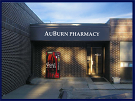 This picture shows the AuBurn Pharmacy Carbondale Location. It is a dark brick building with a dark blue awning on it