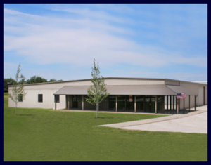 This shows AuBurn Pharmacy Corporate Location. It is a tan metal building with a large metal awning. With a large grass yard with two trees in front.