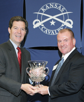 Governor Brownback and Mike Burns pose for a picture holding the award for The Governor's Award of Excellence and Bio-Microbics.