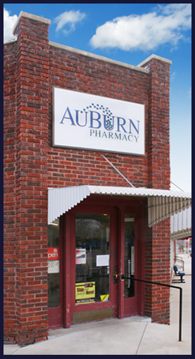 Pictured is The AuBurn Pharmacy Wellsville Kansas Location. This is a all brick building with a large glass door.